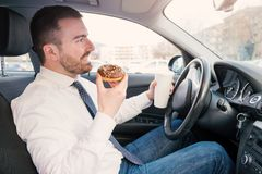 Man having breakfast and driving seated in car Royalty Free Stock Image