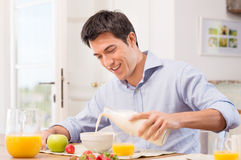 Man Having Breakfast With Milk. Happy Young Man Pouring Milk Into Bowl For Breakfast Royalty Free Stock Photos