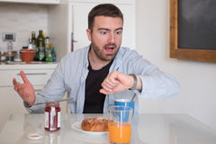Man having breakfast but too late to go to work. Man having breakfast but too late to go to job Stock Photo