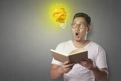 Man Having Bright Idea. Portrait of successful handsome Asian man smiling happy with bright light bulb lamp made of paper, symbol of idea and innovation royalty free stock images