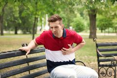 Man having chest pain in park. Heart attack. Young man having chest pain in park. Heart attack royalty free stock photos