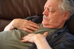 Man having chest pain on sofa stock image