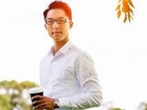 Man having a coffee break in a park Stock Photos