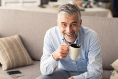 Man having a coffee break. Man relaxing at home on the couch and having a coffee break, he is smiling at camera and holding a cup Stock Photo