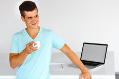Man  having a coffee-break, standing and smiling. Stock Photography