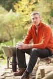 Man Having Coffee Break Whilst Working Outdoors. In Garden stock image