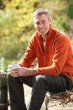 Man Having Coffee Break Whilst Working Outdoors. In Garden stock photography