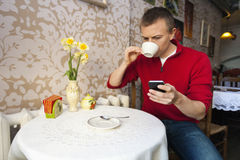 Man having coffee while reading text message on cell phone at cafe Stock Photography