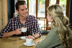 Man having coffee while talking with woman in cafe. Young man having coffee while talking with woman in cafe Stock Photography