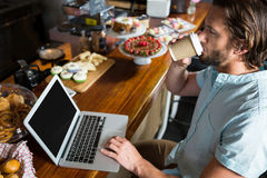 Man having coffee while using laptop at counter Stock Images