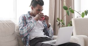 Man having coffee and using laptop at home. African american man drinking coffee and using laptop at home stock video footage