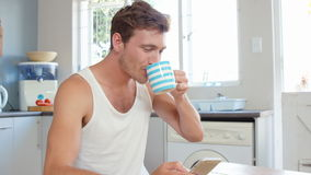 Man having coffee and using smartphone. In kitchen stock video footage