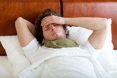Man having cold in bed. Young man having cold lying in bed, horizontal Stock Images