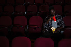 Man having cold drink while watching movie Royalty Free Stock Images