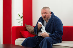 Man having a cold holding tissue with box full of tissues Stock Image