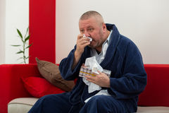 Man having a cold holding tissue with box full of tissues Royalty Free Stock Image