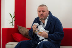 Man having a cold holding tissue with box full of tissues Royalty Free Stock Images