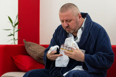 Man having a cold holding tissue with box full of tissues Stock Photo