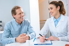 Man having consultation with beautiful oculist writing diagnosis. In clinic stock photo