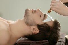 Man having cosmetic mask in salon. Man having cosmetic mask in spa salon stock images