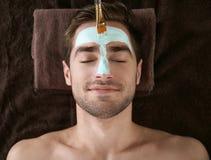 Man having cosmetic mask in salon. Man having cosmetic mask in spa salon stock photos