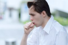 Man is having a cough caused by pollen allergy. In the streets during springtime stock photo