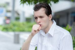 Man is having a cough caused by pollen allergy. During spring time in Tokyo stock photo