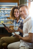 Man having cup of tea and woman using digital tablet in supermarket Royalty Free Stock Photos