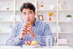Man having dilemma between healthy food and bread in dieting con. Cept Stock Photography