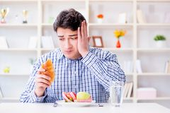 Man having dilemma between healthy food and bread in dieting con. Cept Royalty Free Stock Photography