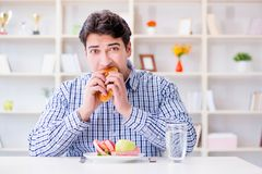 Man having dilemma between healthy food and bread in dieting con. Cept Royalty Free Stock Images