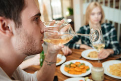 Man having dinner and drinking wine with friends on kitchen stock photo
