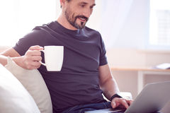Man having drink and working on computer Stock Photo
