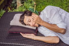 Man having an ear candle therapy against the backdrop of a tropical garden royalty free stock photos