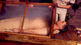 Man having exotic sauna treatment in India spa salon. stock video footage