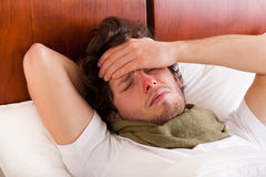 Man having a flu. Young man having a flu lying in bed stock photos