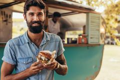 Man having food truck burger. Portrait of happy young men standing near food truck with a burger. Hipster having a delicious burger outdoors royalty free stock photos