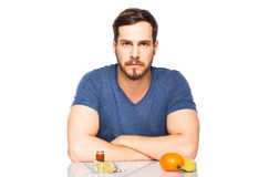 Man having in front pills and fruits, Choosing between them Royalty Free Stock Image
