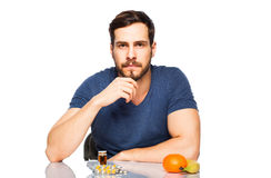 Man having in front pills and fruits, Choosing between them Stock Photos
