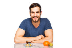 Man having in front pills and fruits, Choosing between them Stock Photography