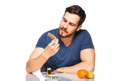 Man having in front pills and orange juice Stock Image