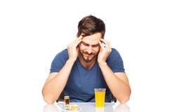 Man having in front pills and orange juice Stock Photos