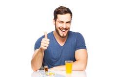 Man having in front pills and orange juice Royalty Free Stock Photos