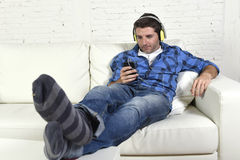 Man having fun alone lying on couch listening to music with mobile phone and headphones Royalty Free Stock Photography