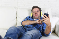 Man having fun alone lying on home couch listening to music with mobile phone and headphones Royalty Free Stock Photos