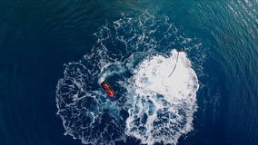 The man is having fun, flying over the water on a flyboard, under the pressure of water. Aerial video shooting, bird`s