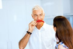 Man holding a red pepper next to his face stock image