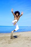 Man having fun jumping on sand in front of the ocean in vacation Royalty Free Stock Photo