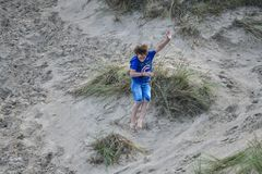 Man having fun on sand beach with grass field and sand dunes during vacations stock photography