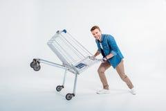 Man having fun with shopping trolley on white. Excited young man having fun with shopping trolley on white Stock Photos